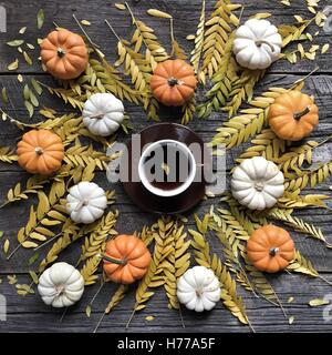 Pumpkins, autumn leaves and cup of coffee - Stock Photo