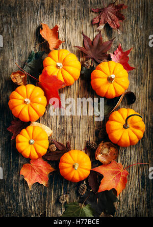 Pumpkins and autumn leaves on wooden table - Stock Photo