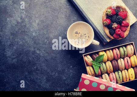 Colorful macaroons and berries on stone table. Sweet macarons and coffee cup. Top view with copy space for your - Stock Photo