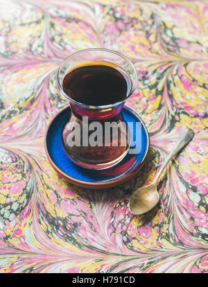 Turkish tea in traditional oriental tulip glass over colorful background - Stock Photo