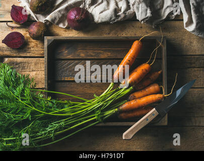 Fresh carrots and beetroots in wooden tray over rustic background - Stock Photo