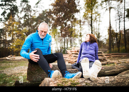 Senior runners sitting on wooden logs, resting. Autumn nature. - Stock Photo