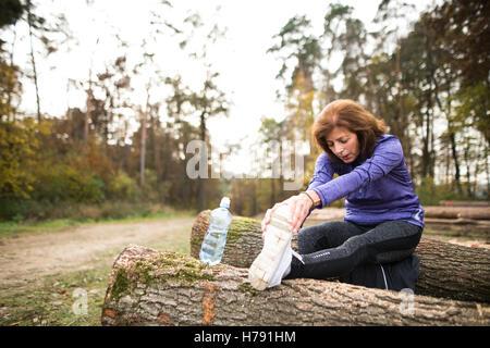 Senior runner sitting on wooden logs, stretching, drinking water - Stock Photo