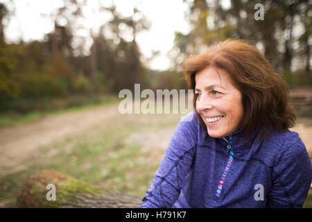 Senior runner sitting on wooden logs, woman resting, smiling. - Stock Photo