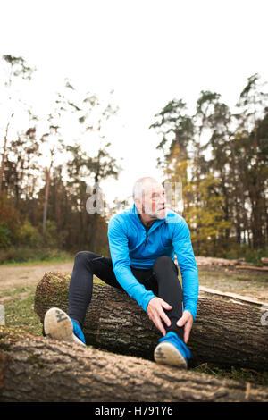 Senior runner sitting on wooden logs, man resting, stretching. - Stock Photo