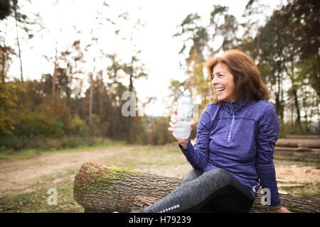 Senior runner sitting on wooden logs, resting, drinking water. - Stock Photo