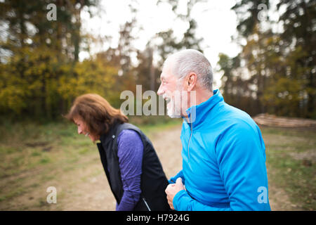 Beautiful senior couple running outside in sunny autumn forest - Stock Photo