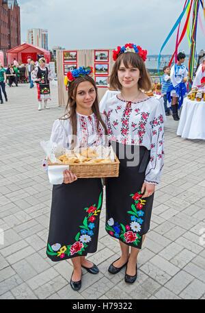 Dnepropetrovsk, Ukraine - September 14, 2013: Girls in Ukrainian national costumes sold buns for charitable purposes - Stock Photo