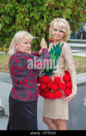Dnepropetrovsk, Ukraine - September 14, 2013: Fashion designer prepares the model for exit at the podium - Stock Photo