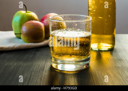 Apple wine in a glass in front of apples on wooden rustic table - Stock Photo