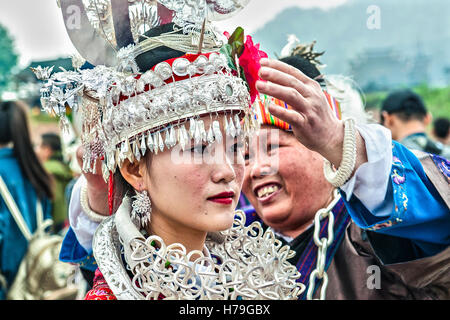 A mother fix up the headdress of her daughter before the parade of the Sister's meal Festival at Shidong, in Guizhou - Stock Photo