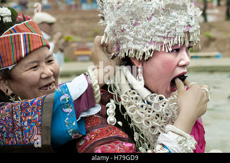 Mother fixes up the headdress of her daughter eating before the parade of the Sisters' Meal Festival in Shidong, - Stock Photo