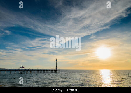 People on Brighton Jetty at sunset on a summer evening - Stock Photo