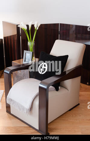 Black cushion with symbol on dark wood polished armchair with half-folding-screen - Stock Photo