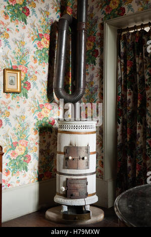Vintage stove in corner of room with floral wallpaper in 18th century Chateau de Cussigny, Cote d'Or, Bourgogne, - Stock Photo
