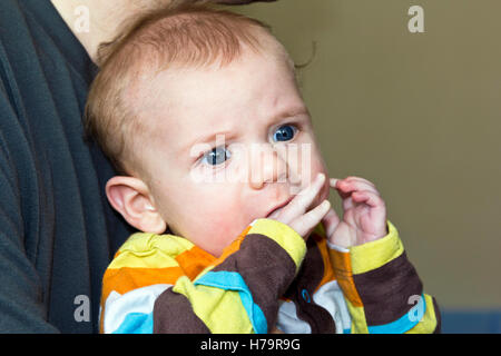 Baby boy chewing his own fingers when teething - Stock Photo