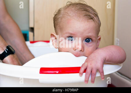 Baby boy teething and having a bath - Stock Photo