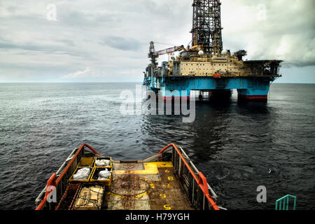 Anchor-handling Tug/Supply (AHTS) vessel during dynamic positioning (DP) operations near Oil Rig. - Stock Photo