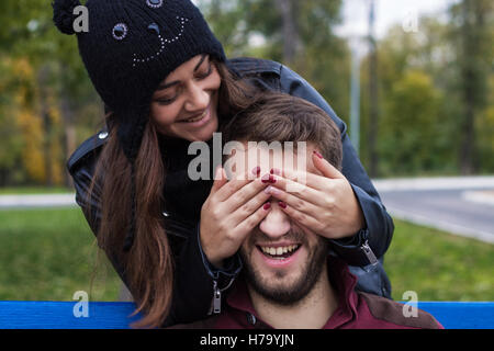 Closeup shot of young beautiful laughing stylish couple in autumn park. They look happy. She is kissing him. He - Stock Photo