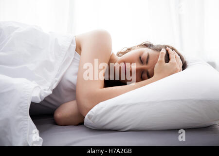 Young beautiful Caucasian woman on bed having headache / insomnia / migraine / stress - Stock Photo