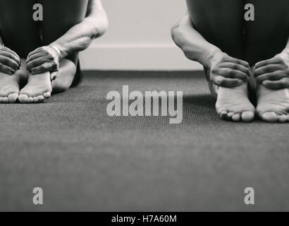 Series of monochromatic photographs taken in a yoga studio. These images explore  the yogic grips in a yoga class. - Stock Photo