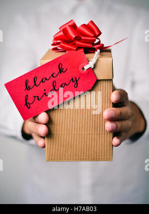 closeup of a young caucasian man in a white shirt holding a gift box with a red label tied to it with the text happy - Stock Photo