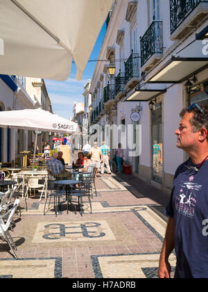 Portugal Algarve 4th c BC ancient old city port Faro typical mosaic road lane with cafe tourists shop shops store - Stock Photo