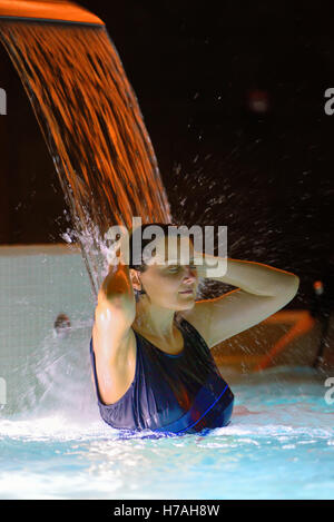 Woman relaxation in pool with waterfall - Stock Photo