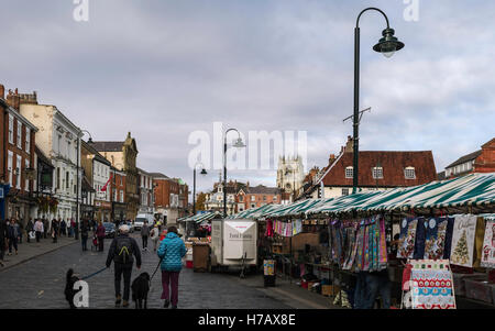 Town centre on market day with view of shops, cars, public, and St Mary's church on an overcast day in autumn. - Stock Photo