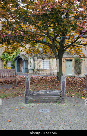Old penal stocks in front of cottages in autumn. Stow on the Wold, Gloucestershire, England - Stock Photo