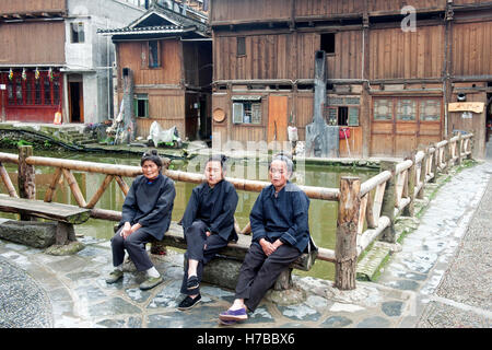 Three Dong women rest in front of the stream flowing near their wood houses, in Zhaoxing, Guizhou province, China - Stock Photo