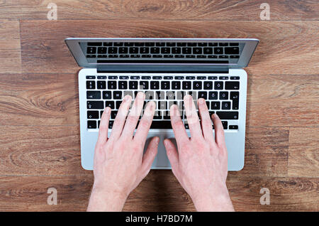 Young Adult Man Sitting on Floor with Hands on the Keyboard of a Notebook Computer, Typing - Stock Photo