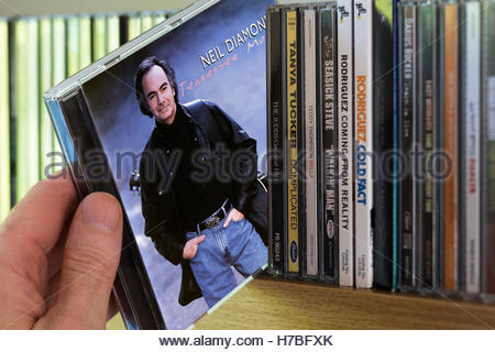 Tennessee Moon, Neil Diamond CD being chosen from a shelf of other CD's - Stock Photo