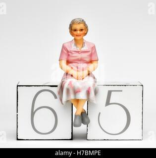 A figurine female pensioner sitting on the number 65 retirement concept. - Stock Photo