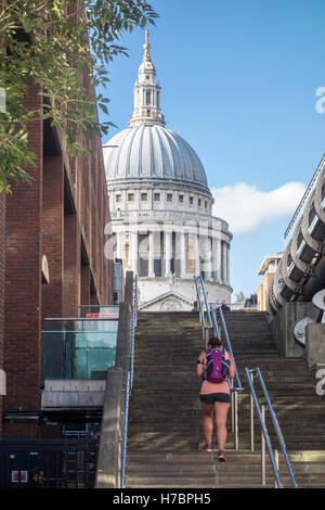 Young female jogger walking up the steps next to Millennium Bridge towards St Paul's Cathedral. City of London, - Stock Photo