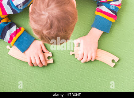 Child playing with wooden toy railroad tracks. Piecing together two parts. Concept of childhood learning and problem - Stock Photo