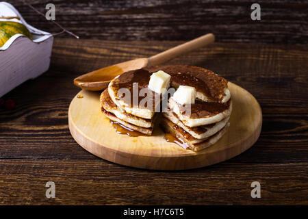 Homemade pancakes served warm with butter and maple syrup on rustic wooden table - Stock Photo
