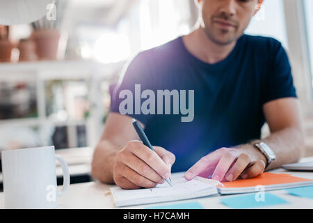 Young businessman writing down important notes in diary at his desk. Young businessman writing in his notepad. - Stock Photo