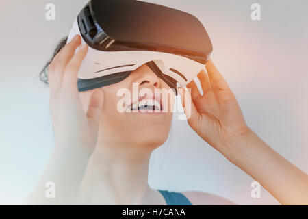 Close up of young woman in virtual reality headset looking at the objects. Female model with virtual reality goggles - Stock Photo