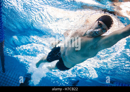 Man swimming the front crawl in a pool. Underwater shot of professional swimmer practising for race in swimming - Stock Photo
