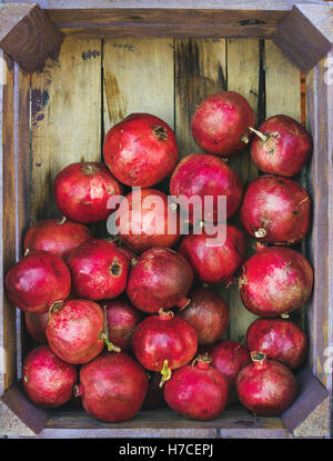 Turkish ripe red pomegranates in rustic wooden box, top view, copy space, vertical composition - Stock Photo