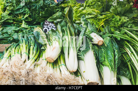 Various fresh green vegetables and herbs on market stall with price label in German at food market in Vienna - Stock Photo
