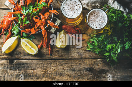 Two mugs of wheat beer and boiled crayfish in pan served with with lemon and parsley over rustic wooden background, - Stock Photo