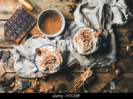 Hot chocolate with whipped cream and cinnamon sticks served with anise, nuts and cocoa powder on rustic wooden background, - Stock Photo