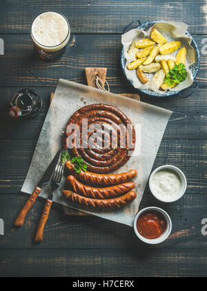 Grilled sausages with sauces, roasted potato and glass of dark beer on rustic wooden serving board over dark scorched - Stock Photo