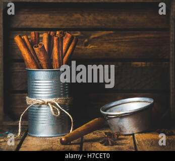 Cinnamon sticks in can tied with rope, anise stars and sieve on rustic wooden background, copy space - Stock Photo