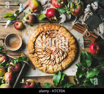 Apple crostata pie with cinnamon served with fresh garden apples with leaves on rustic wooden background, top view, - Stock Photo