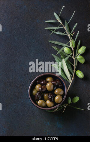 Bowl of green and black olives with young olives branch over black textural background. Overhead view with space - Stock Photo