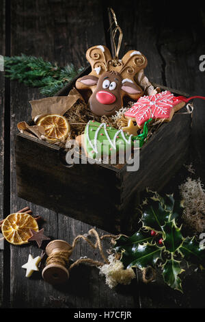 Christmas Handmade patterned gingerbreads as Christmas tree, reindeer Rudolph and snowflake shapes in wooden box - Stock Photo