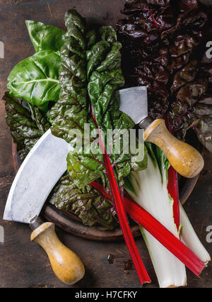 Variety of fresh chard mangold salad leaves on woode chopping board with vintage knife over old dark wooden background. - Stock Photo
